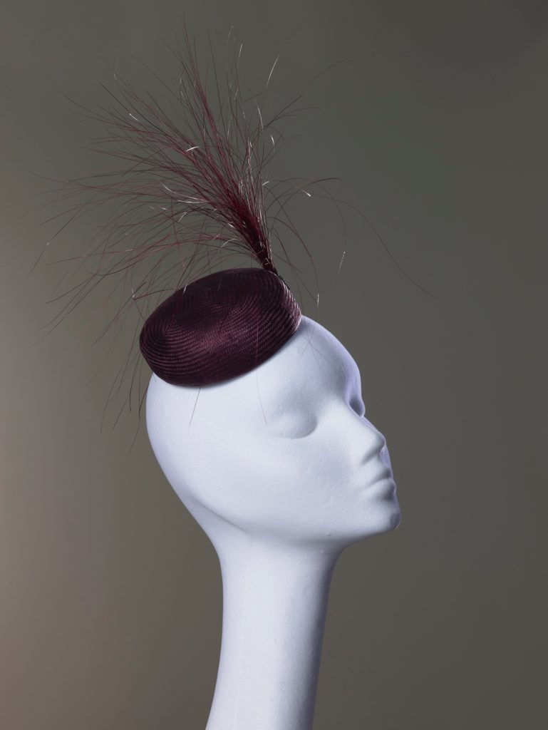 Burgundy parasisal straw button hat with peacock brush trim