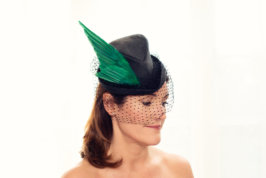 Black sisal straw perching hat with silk veiling and green wing