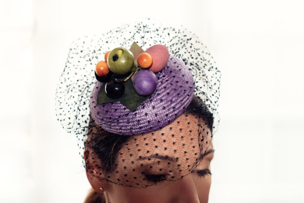 Lilac straw button hat with silk veiling and fruit