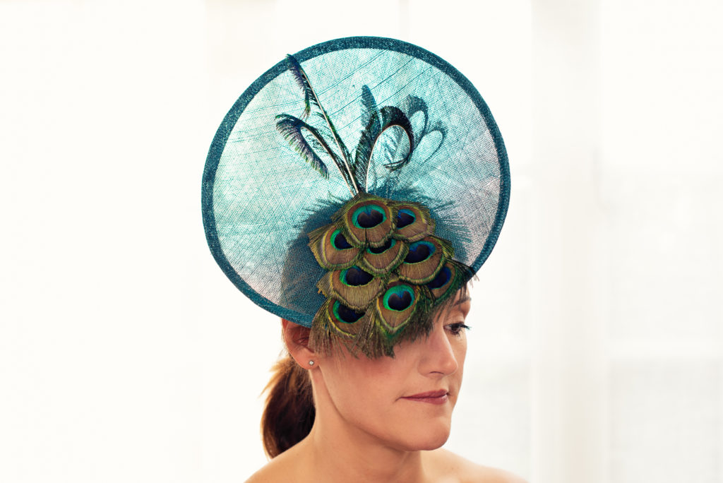 Teal sinamay disc hat with peacock feathers