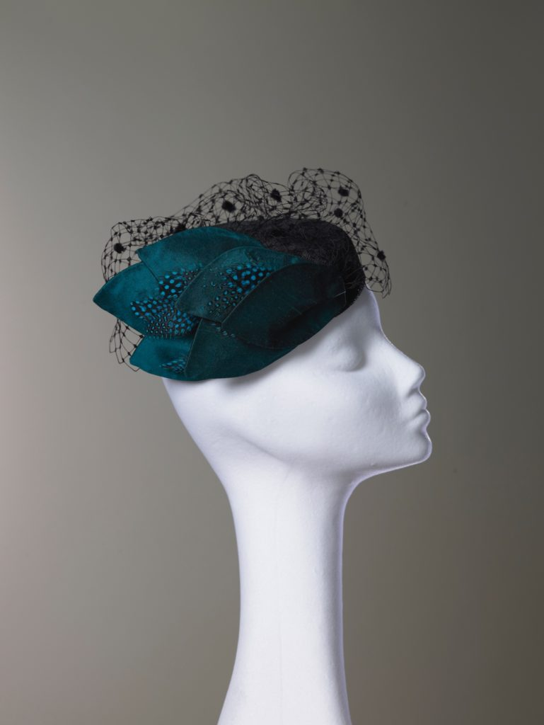 Black sinamay pillbox hat with silk leaves and veiling side view