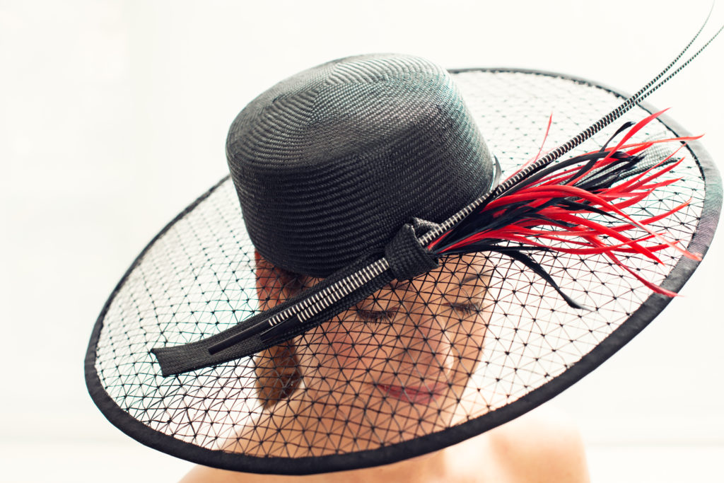 Black parasisal hat with wide sinamay brim, quills and goose feathers